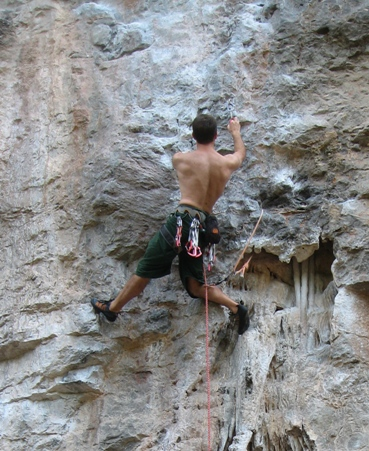 Leaning off a straight left arm (hidden), twisting the right hip into the rock and reaching up with the right hand.