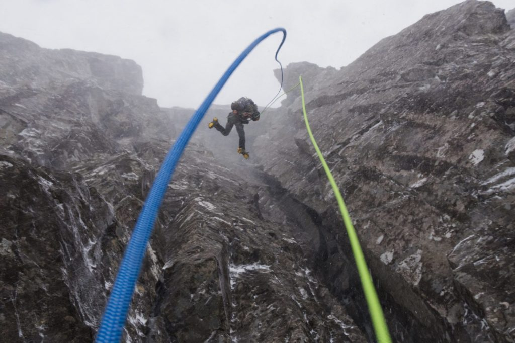 Abseiling on a winter mountain in Glen Coe, Scotland.