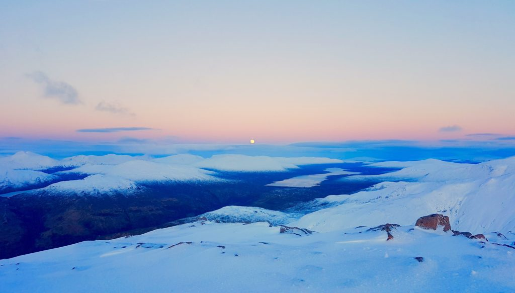 Moon rising over snow on Rannoch Moor, a mountain in Scotland.