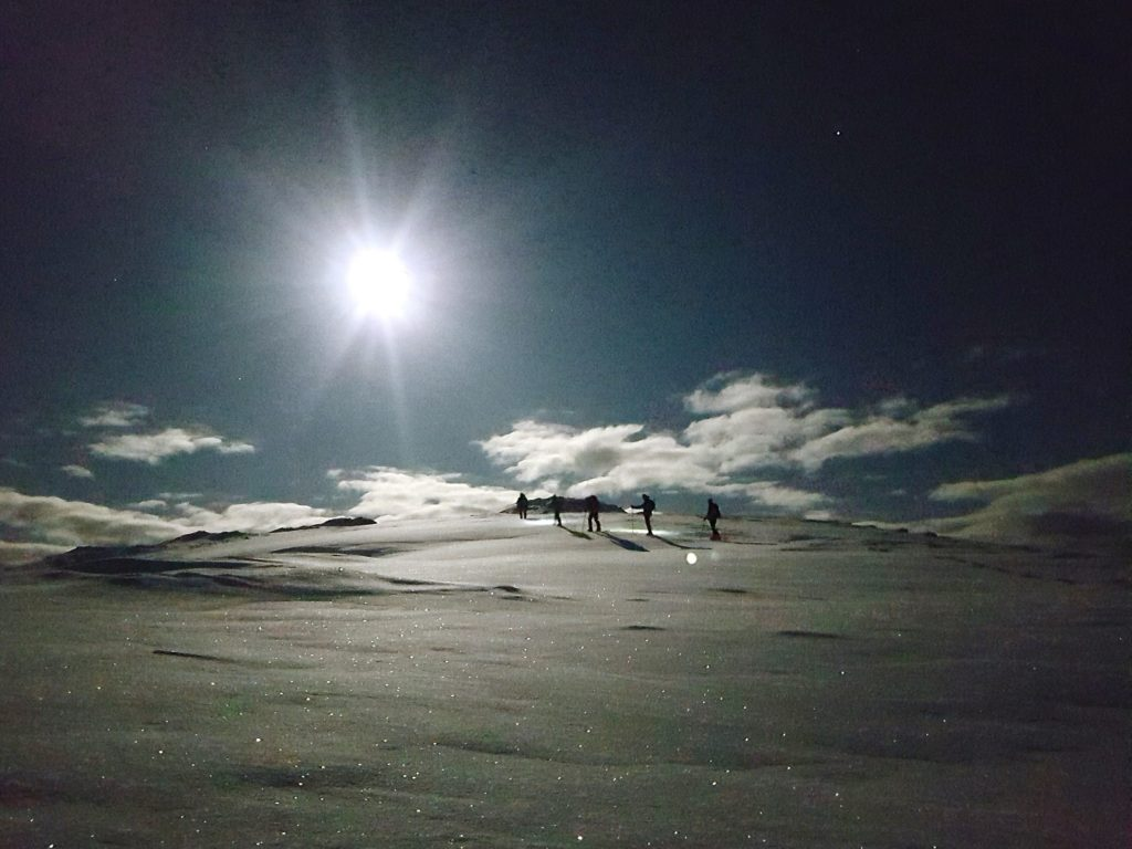 Winter mountain walking at night under moonlight, in Scotland.