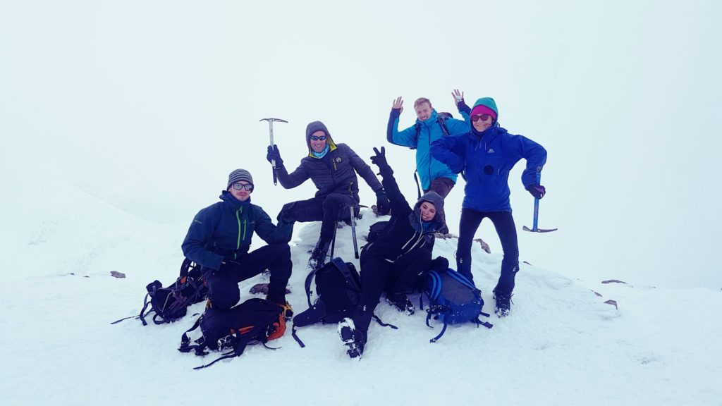Winter walking group on the summit of Stob Dubh, Glen Coe in Scotland.