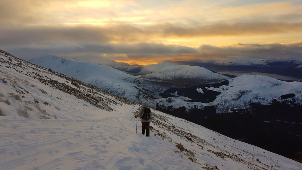Walking through snow on Ben Nevis with a view of sunset over mountains on the horizon.